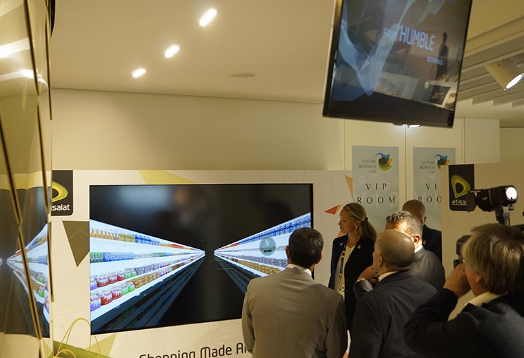 Visitors at the Etisalet exhibition stand view and engage with the interactive touch screen technology